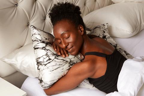 woman asleep holding a bilssy pillowcase for better skin